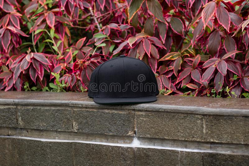 Blank black snapback hat cap flat visor for mockup. Blank snapback hat cap flat visor with black color in outdoor, ready for your mock up design or presentation stock images