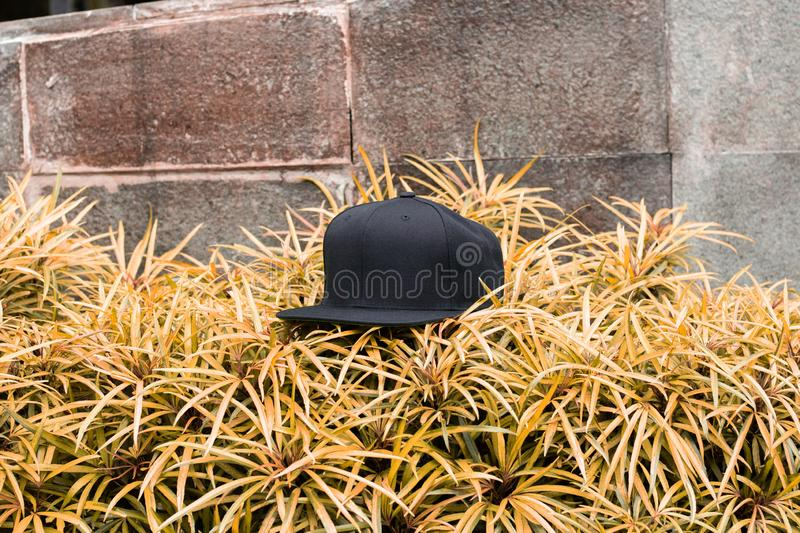 Blank black snapback hat cap flat visor for mockup. Blank snapback hat cap flat visor with black color in outdoor, ready for your mock up design or presentation royalty free stock photos
