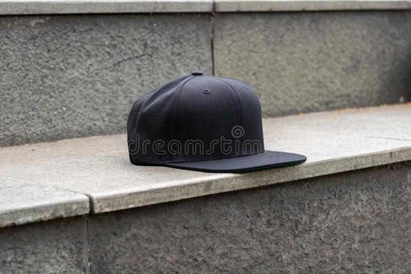 Blank black snapback hat cap flat visor for mockup. Blank snapback hat cap flat visor with black color in outdoor, ready for your mock up design or presentation stock photo