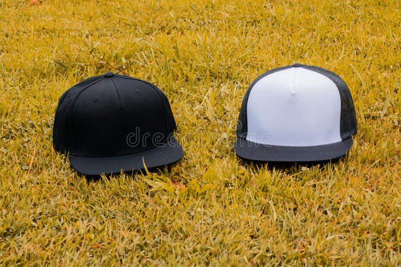 Blank black snapback and trucker hat cap flat visor for mockup. Blank trucker hat and snapback hat cap flat visor with black and white color in outdoor, ready stock image