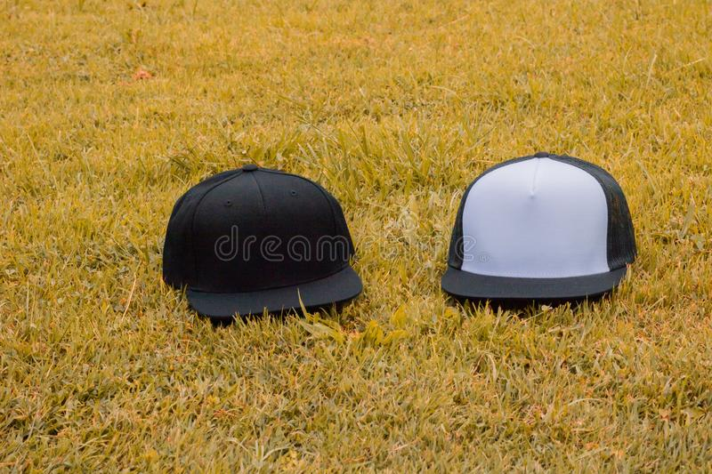 Blank black snapback and trucker hat cap flat visor for mockup. Blank trucker hat and snapback hat cap flat visor with black and white color in outdoor, ready stock photography
