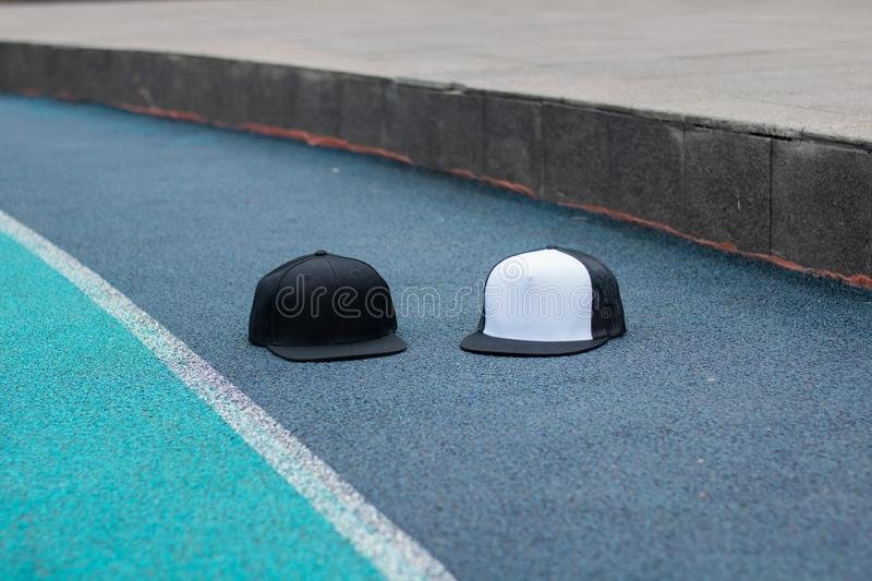 Blank black snapback and trucker hat cap flat visor for mockup. Blank trucker hat and snapback hat cap flat visor with black and white color in outdoor, ready royalty free stock image