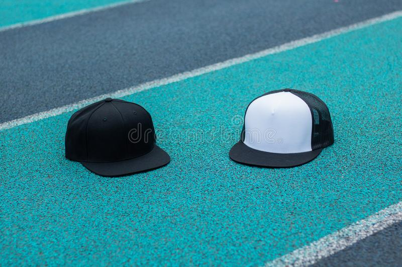 Blank black snapback and trucker hat cap flat visor for mockup. Blank trucker hat and snapback hat cap flat visor with black and white color in outdoor, ready stock photos