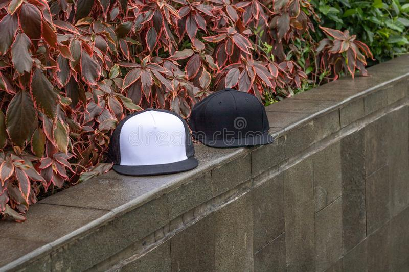 Blank black snapback and trucker hat cap flat visor for mockup. Blank trucker hat and snapback hat cap flat visor with black and white color in outdoor, ready royalty free stock images