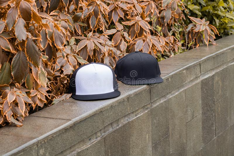 Blank black snapback and trucker hat cap flat visor for mockup. Blank trucker hat and snapback hat cap flat visor with black and white color in outdoor, ready royalty free stock photo