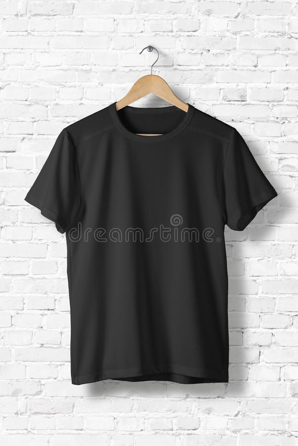 Blank Black T-Shirt Mock-up hanging on white wall, front side view. royalty free stock photos