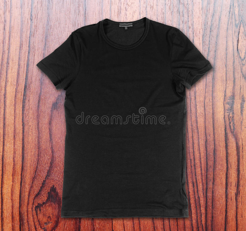 Blank black t-shirt on the wooden background stock images