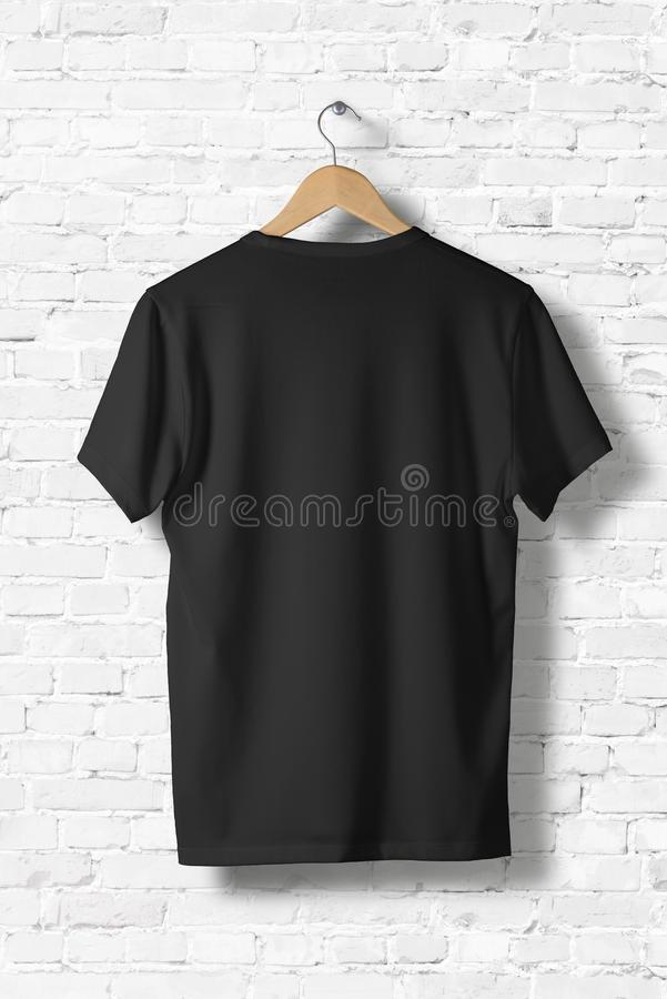 Blank Black T-Shirts Mock-up hanging on white wall, rear side view. stock images