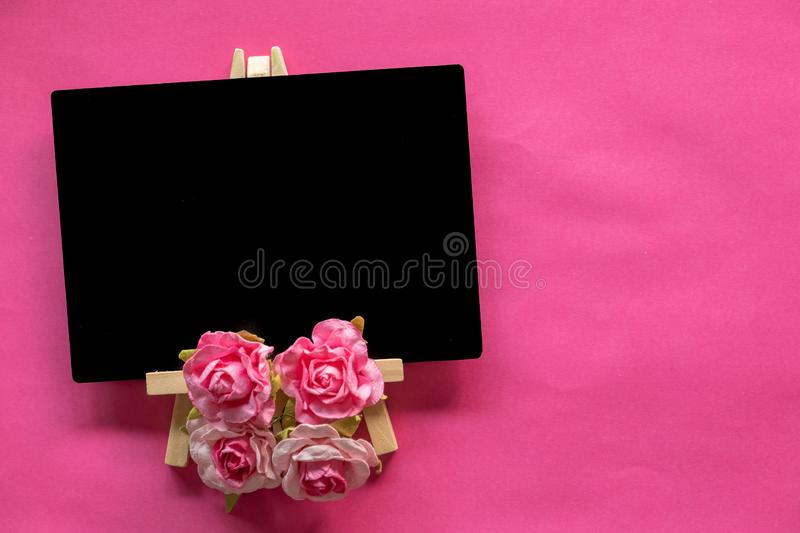 blank blackboard and pink flower on pink background with copy space, Valentines Day concept stock images