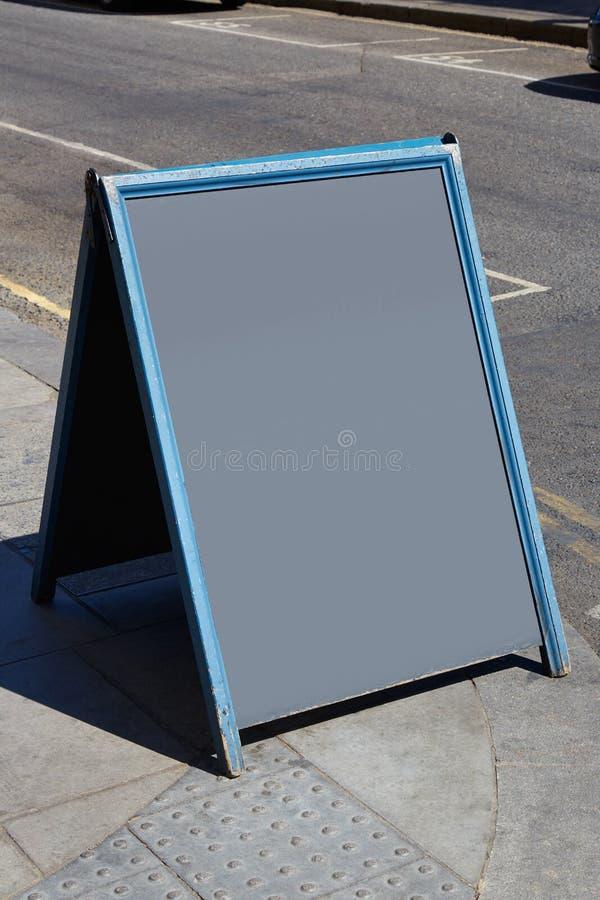 Blank blackboard in a sunny street stock images