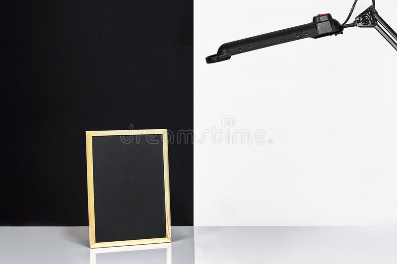 Blank Blackboard On Table Near White And Black Wall. Stock Image ...