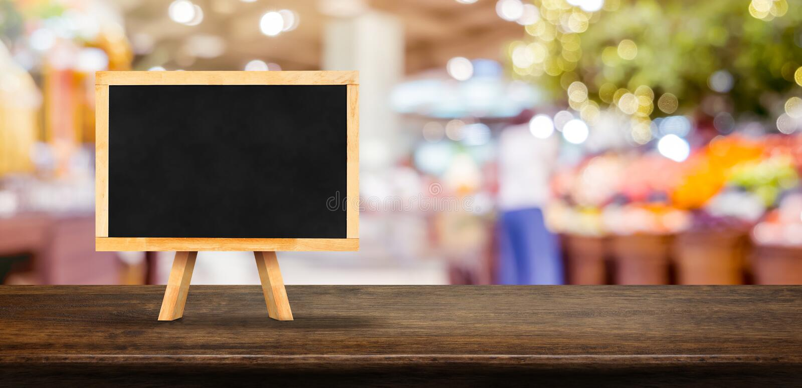 Blank blackborad on wooden table top with blur people shopping at supermarket bokeh background,Mock up for display or montage of royalty free stock images
