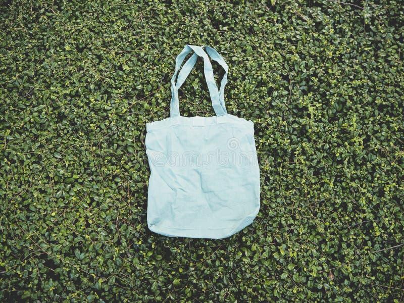 Blank blue Mockup Linen Cotton Tote Bag on Green Bush Trees Foliage Background royalty free stock photos