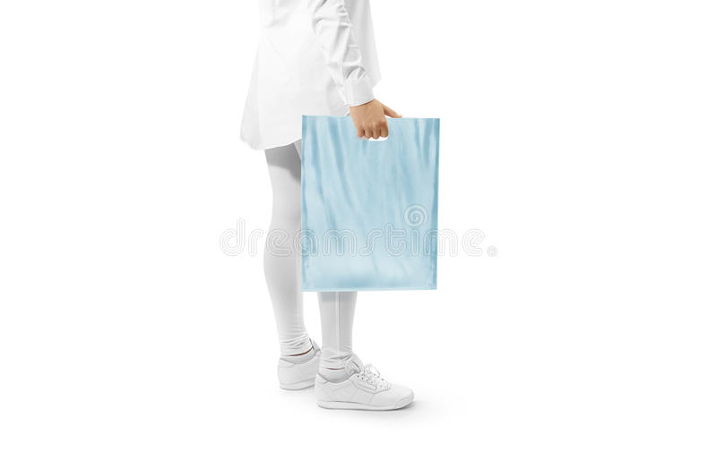 Blank blue plastic bag mockup holding hand. Woman hold plain carrier sac mock up. Polythene bagful branding template. Shopping carry package in persons arm stock photography