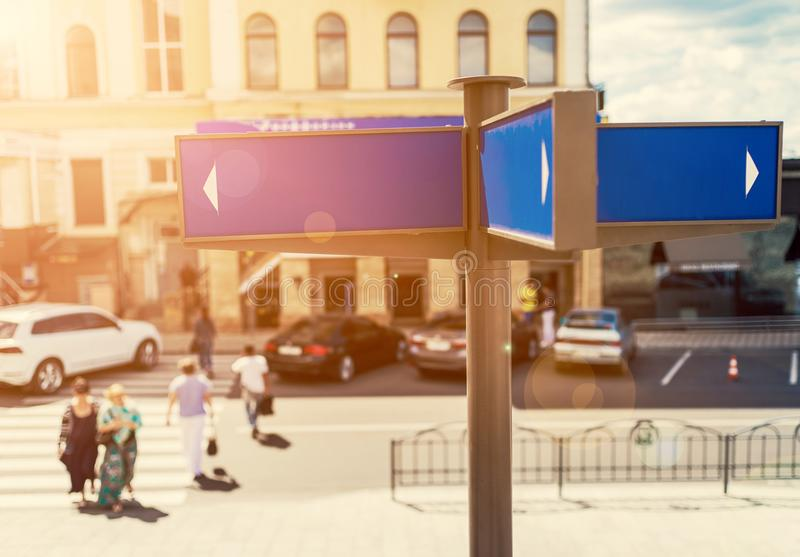 Blank blue street signs with city and people in blur on background, free space for text. royalty free stock image