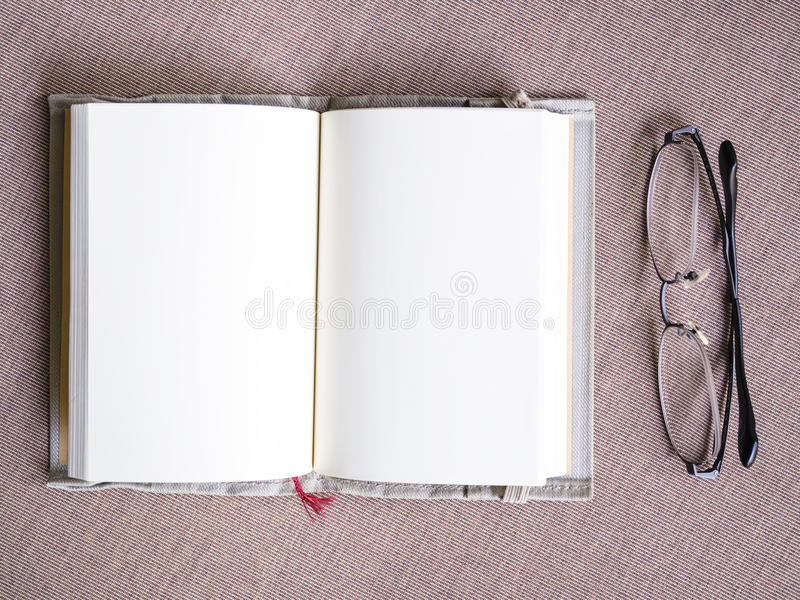 Blank book page open spread with eyeglasses on table stock photo