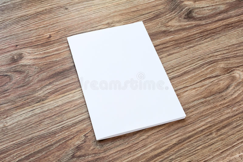 Blank of brochure is on a wooden desk. stock image
