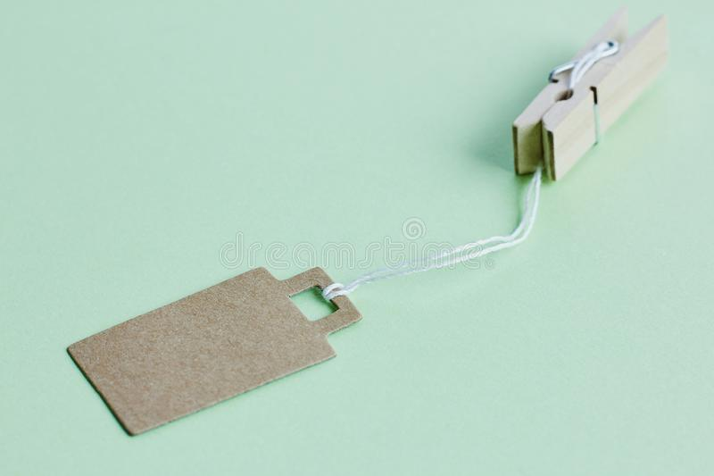 Blank brown cardboard price tag, sale tag, gift tag, address label hanging on clothes wooden clips on pastel green background. Blank brown cardboard price tag stock photography