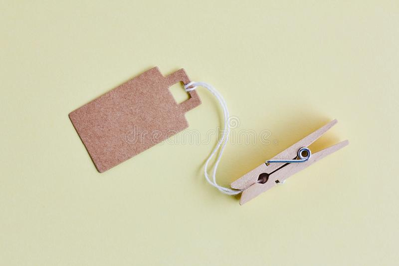 Blank brown cardboard price tag, sale tag, gift tag, address label hanging on clothes wooden clips on pastel yellow background. Blank brown cardboard price tag royalty free stock photography