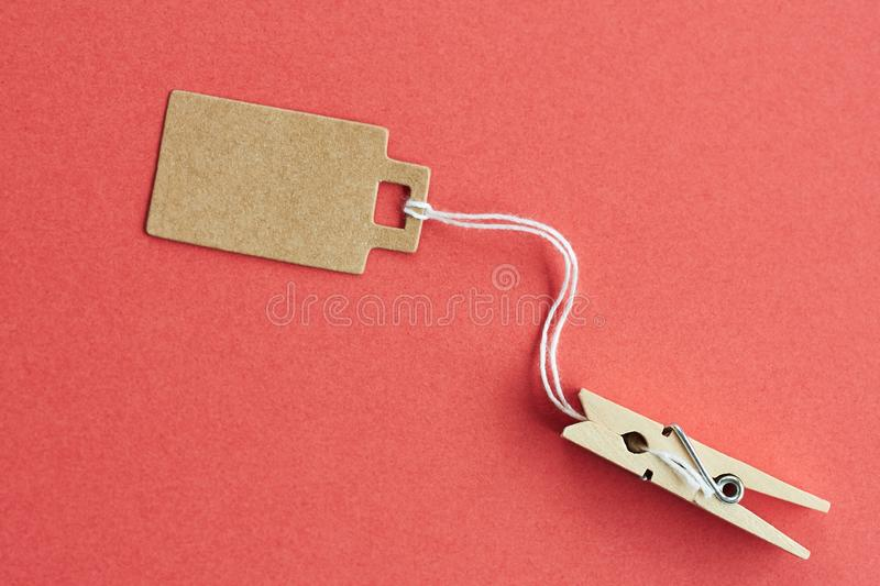 Blank brown cardboard price tag, sale tag, gift tag, address label hanging on clothes wooden clips on red background. Blank brown cardboard price tag, sale tag royalty free stock image