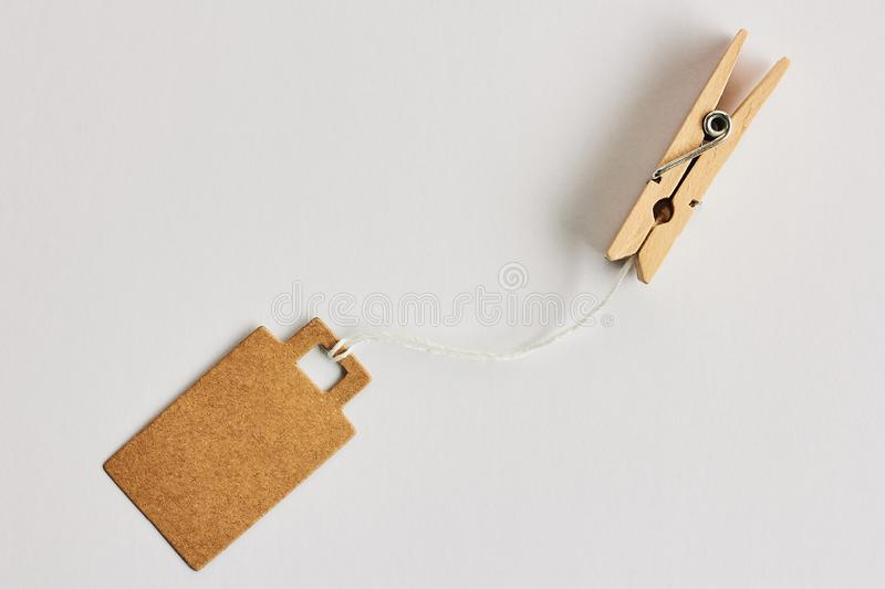 Blank brown cardboard price tag, sale tag, gift tag, address label hanging on clothes wooden clips on white background. Blank brown cardboard price tag, sale tag stock photography