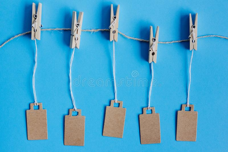 Blank brown cardboard price tags, sale tag, gift tag, address label hanging on clothes wooden clips on blue background. Blank brown cardboard price tags, sale royalty free stock images