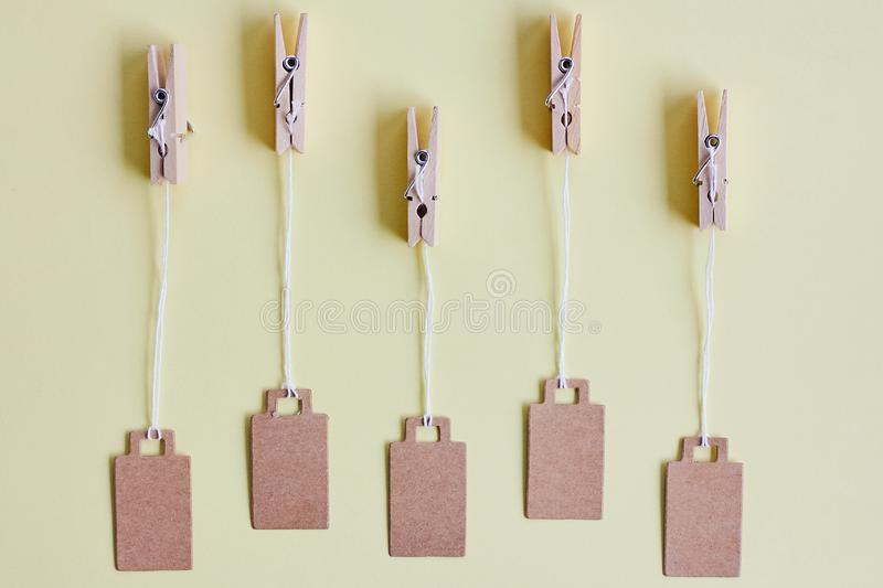 Blank brown cardboard price tags, sale tag, gift tag, address label hanging on clothes wooden clips on pastel yellow background. Blank brown cardboard price tags stock images