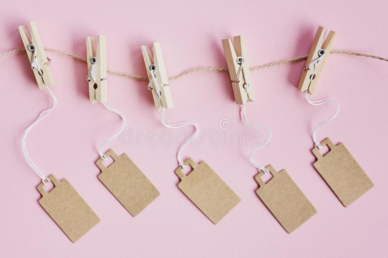 Blank brown cardboard price tags, sale tag, gift tag, address label hanging on clothes wooden clips on pink background. Blank brown cardboard price tags, sale royalty free stock photos