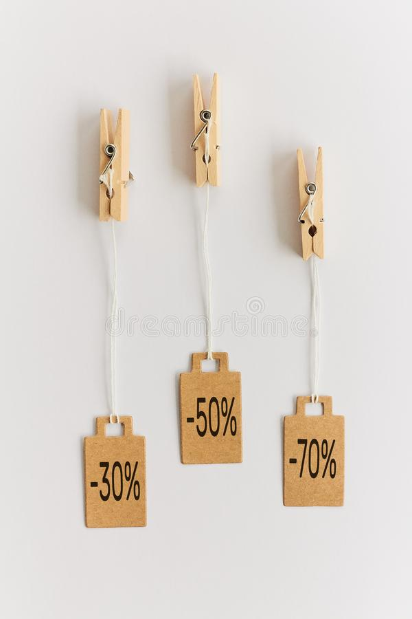 Blank brown cardboard price tags, sale tag, gift tag, address label hanging on clothes wooden clips on white background. Blank brown cardboard price tags, sale stock photos
