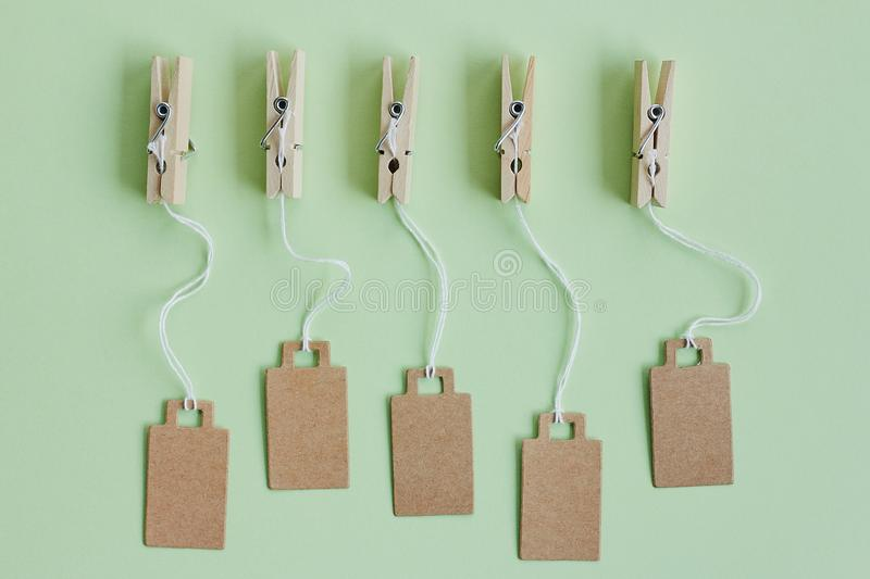 Blank brown cardboard price tags, sale tag, gift tag, address label hanging on clothes wooden clips on pastel green background. Blank brown cardboard price tags stock photo