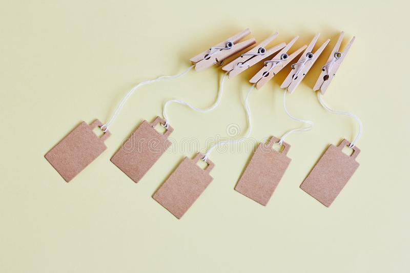 Blank brown cardboard price tags, sale tag, gift tag, address label hanging on clothes wooden clips on pastel yellow background. Blank brown cardboard price tags stock photography