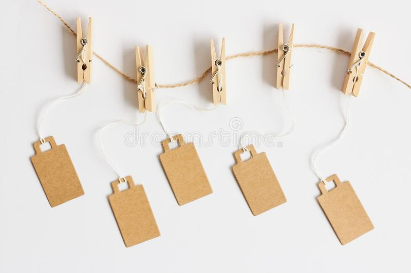 Blank brown cardboard price tags, sale tag, gift tag, address label hanging on clothes wooden clips on white background. Blank brown cardboard price tags, sale royalty free stock photo