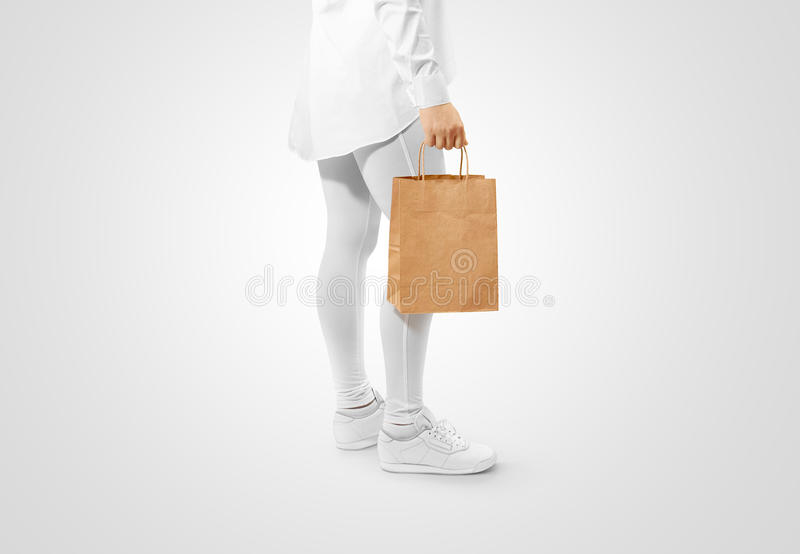 Blank brown craft paper bag design mockup holding hand. Clipping path. Woman hold kraft textured purchase pack mock up. Clear shop bagful branding template royalty free stock photography