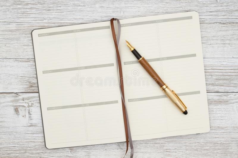 Blank brown day planner with pen on a weathered whitewash wood background stock image