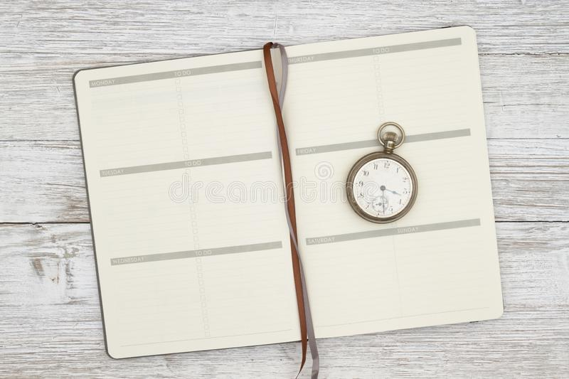Blank brown day planner with pocket watch on a weathered whitewash wood background stock photos