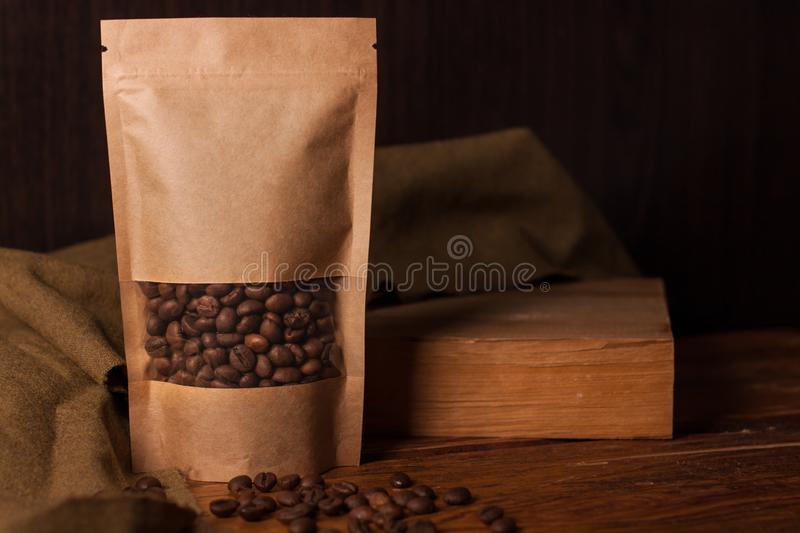 Blank brown kraft paper pouch bag with coffee beans in transparent window on wooden background. Trendy packaging for tea. Blank brown kraft paper pouch bag with stock photo