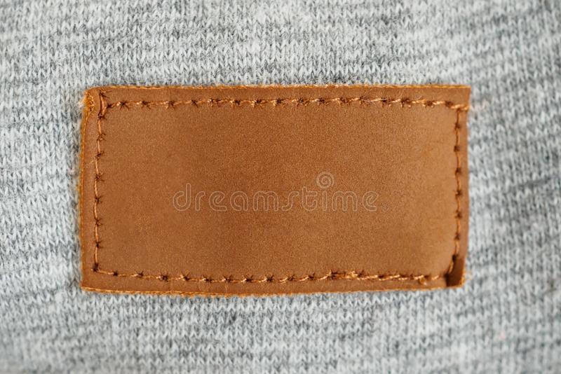 Blank brown leather cloth label on gray fabric. Textile background royalty free stock images