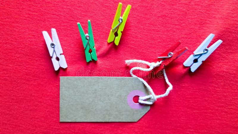 Blank brown note on a clothesline and red background for design in your christmas, black friday concept, valentines day royalty free stock photography