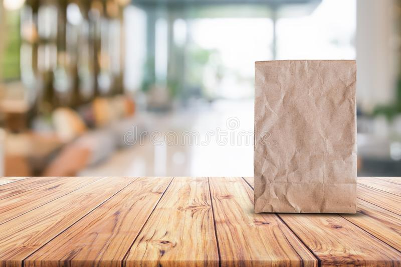 Blank brown paper bag for taking away food on wood table blurred abstract background interior view for branding mockup stock photos