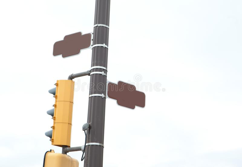 Blank brown street signs and traffic lights. Corner or intersection with traffic lights and two brown street signs with copy space stock images