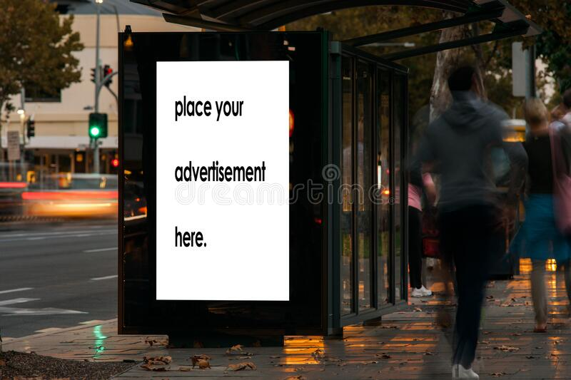Blank bus shelter advertising boardat twighlight royalty free stock photography