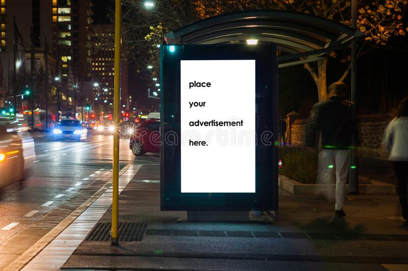 Blank bus shelter advertising boardat twighlight stock image