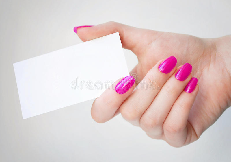 Blank Business Card. In elegant female hand with pink nails. Isolated