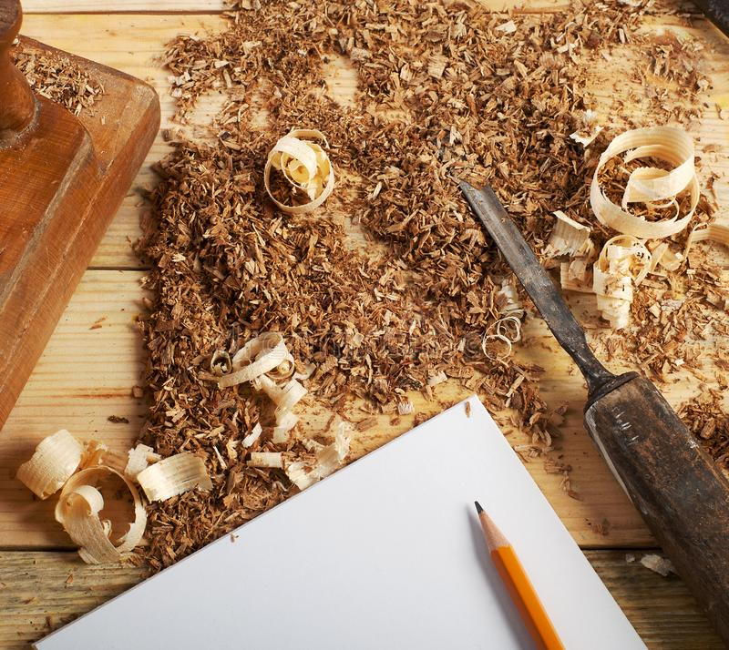 Business card on wooden table for carpenter tools with sawdust. royalty free stock image