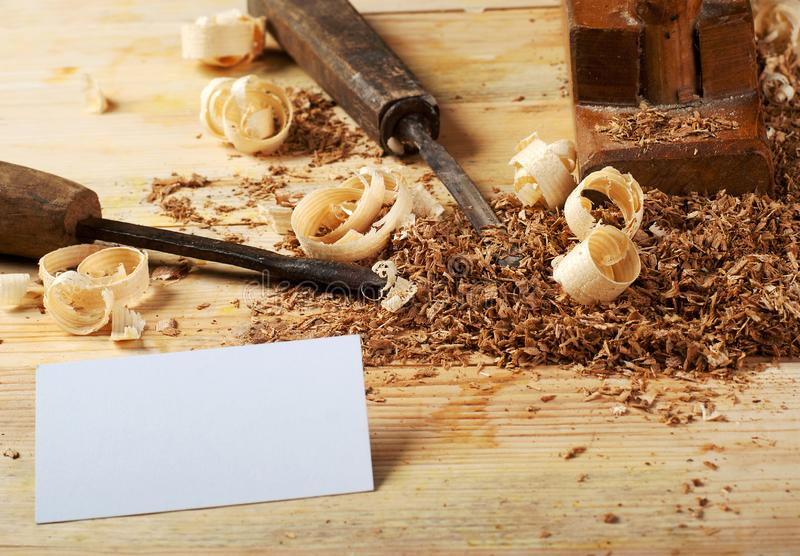 Business card on wooden table for carpenter tools with sawdust. royalty free stock images
