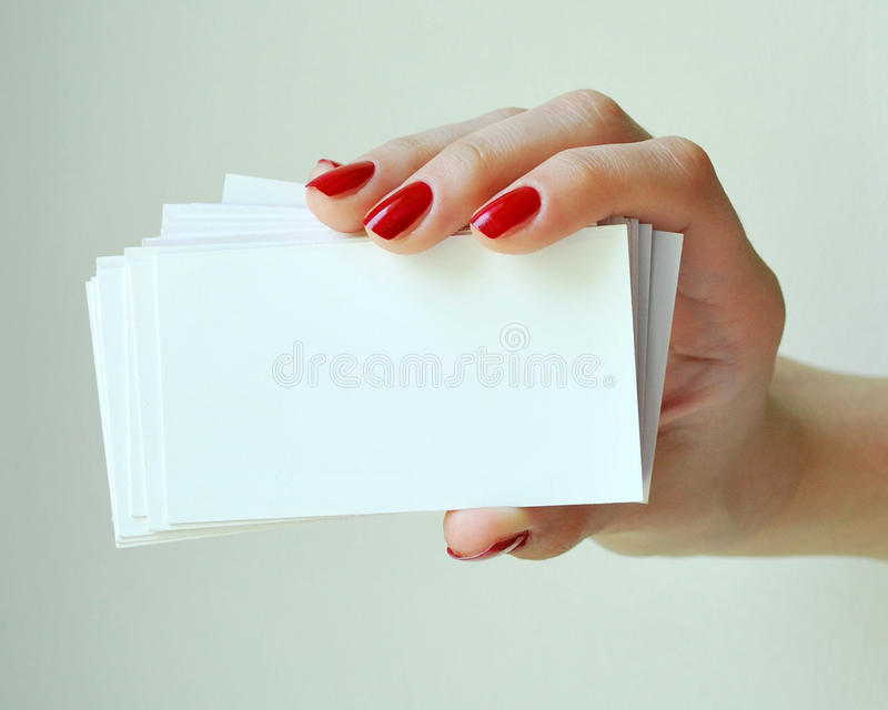 Blank Business Cards. In elegant female hand with red nails. Isolated