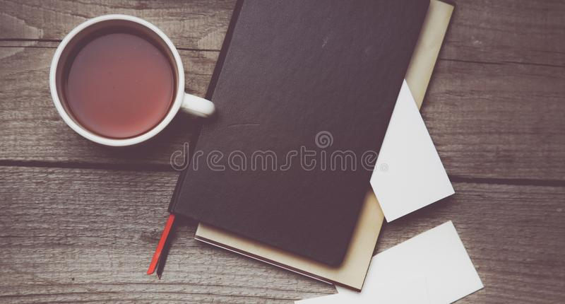 Blank business cards with pen, notebook and tea cup on wooden office table.  stock photos