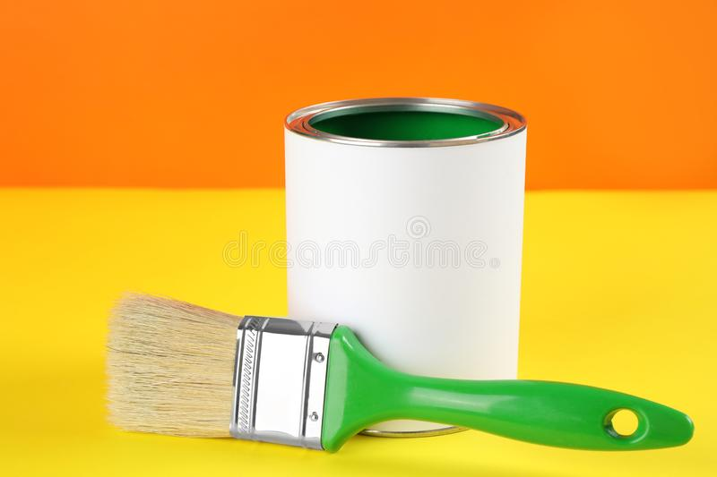 Blank can of paint with brush. On color background royalty free stock images