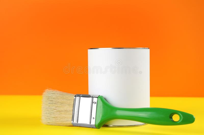 Blank can of paint with brush on table. Against color background stock image