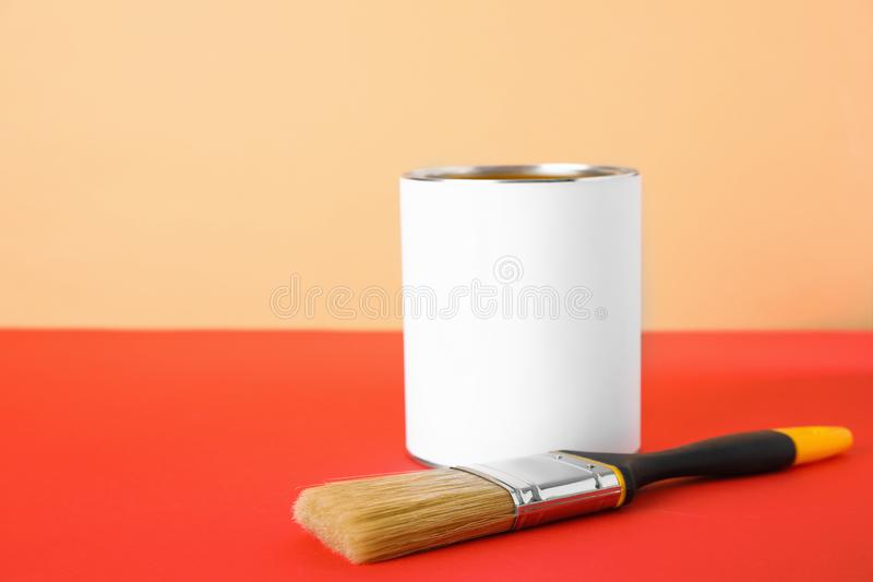 Blank can of paint with brush on table. Against color background stock photography